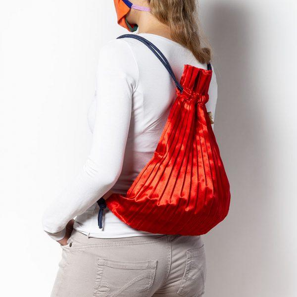 zainetto plissettato in raso rosso indossato
