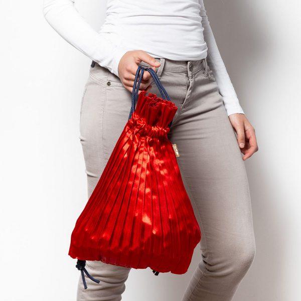 zainetto plissettato in raso rosso tenuto in mano